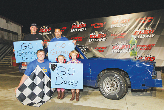 Dan Heyda, front left, enjoys the spoils of victory as he takes part in the Elko Speedway tradition of posing for a photo after winning the Driving for Excellence fundraiser race for Holy Cross School in Webster. Joining him are, clockwise from upper left, his father, Chris Heyda; father-in-law, Greg Skluzacek; and daughters, Anna and Ellie, who attend Holy Cross School. Dave Hrbacek/The Catholic Spirit