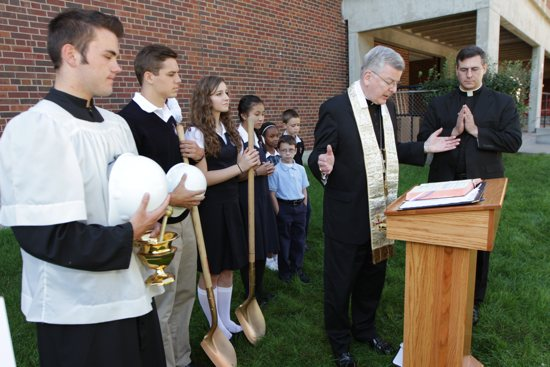 Archbishop John Nienstedt, second from right, prays a blessing at Saint Agnes School in St. Paul at the beginning of a ground-breaking ceremony Sept. 2 that kicked off a new building project at the school. Thanks to a generous gift of more than $10 million by local philanthropist John Nasseff and his wife, Helene Houle, the school will add a $16.7 million student activities center. It is scheduled to be completed by the fall of 2015 and will include a new auditorium plus an expanded gymnasium. Nasseff and Houle were on hand for the groundbreaking, along with their son, Art, and Larry McGough of McGough Construction. From left are Saint Agnes students Anthony Larson (senior), Seamus Ryan (senior) Bridget Hobbs (senior), Angie Nguyen (eighth grade), Malani Sandifer (third), Benedict Berthiaume (third) and Mikael Dahlstrom (fifth). At far right is Father Mark Moriarty, pastor of Saint Agnes.