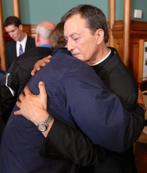 Father Charles Lachowitzer hugs an abuse survivor after the press conference. Dave Hrbacek/The Catholic Spirit