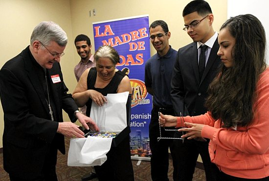 Archbishop John Nienstedt, left, receives a gift from a group of Latino youth at La Familia/Latino education summit Sept. 27 in St. Paul. The group includes Yorki Ramirez (second from left), Carmen Robles (holding gift), Rafael Alvarez, Manuel Hernandez and Carissa Ontiveros. Dave Hrbacek/The Catholic Spirit