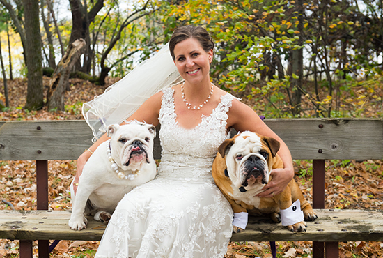Natalie King poses with her English bulldogs Griffin and Olivia on her wedding day. King, the executive director of Catholic Youth Camp on Big Sandy Lake near McGregor, was married at camp on Oct. 4. Photo by Angela Divine Photography