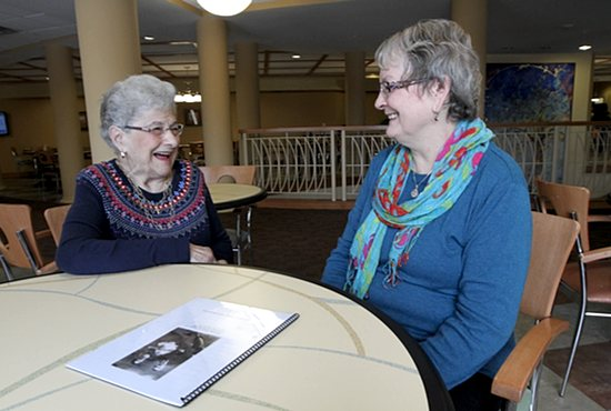 Mary Cox (left), a resident of Carondelet Village in St. Paul, talks with Linda Crosby in the dining area. The two meet regularly through a program called Carondelet Companions, in which Crosby serves as a volunteer. Dave Hrbacek/The Catholic Spirit
