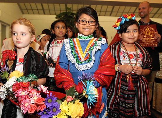 GUADALUPE FEAST Sofia Brazil, (front row, left), her sister, Alayna, and Chelsy Solis prepare for the start of Mass to celebrate the feast of Our Lady of Guadalupe Dec. 12 at Risen Savior in Burnsville. Bishop Andrew Cozzens celebrated the Mass, along with Father Thomas Krenik, pastor of Risen Savior. The Mass included Aztec dancers and a re-enactment of the apparition of Mary to St. Juan Diego performed by youth in the parish. At far right is Scott Brazil, father of Sofia and Alayna. The three belong to Risen Savior, while Solis attends Santa Rosario (Holy Rosary) in Minneapolis.  Dave Hrbacek/The Catholic Spirit