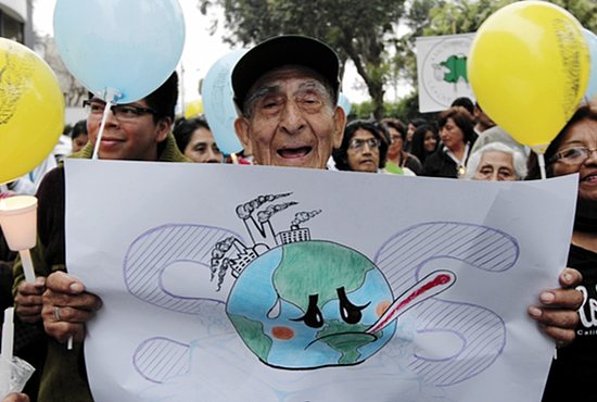 CLIMATE CHANGE Valerio Mendoza, 83, joins a Nov. 30 vigil for climate change on the eve of the U.N. climate summit in Lima, Peru. During the 12-day summit, negotiators will try to finish drafting an agreement to reduce greenhouse gas emissions and help countries adapt to climate change. Mendoza is among parishioners from Lima's Santa Cruz who have been studying about the stewardship of creation and spearheading campaigns to clean up neighborhoods and promote recycling. CNS/Barbara Fraser