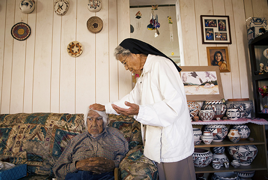 Pueblo Indian Sister Mary Rosita Shiosee prays with a homebound man in Mesita, N.M. CNS/Nancy Wiechec