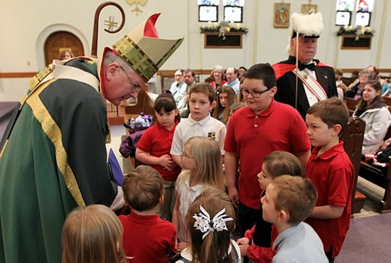CELEBRATION BEGINS Students at Most Holy Redeemer School in Montgomery talk with Archbishop John Nienstedt after presenting the gifts during Mass Jan. 25 at Most Holy Redeemer Church. The archbishop celebrated Mass and helped kick off Catholic Schools Week. Dave Hrbacek/The Catholic Spirit