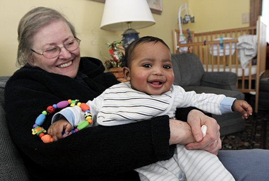 "Nabeel, a 6-month-old boy whose mother moved into Philomena House while she was pregnant, enjoys some bouncy time with house mother Sharon King, who belongs to St. Agnes in St. Paul. ""I just do whatever needs doing,"" said King, who lives at the house with four women and two babies. ""I make sure we have food. I run the girls out shopping, I run them to their OB appointments. Whatever they need, I try to provide and take care of them."" Dave Hrbacek/The Catholic Spirit"