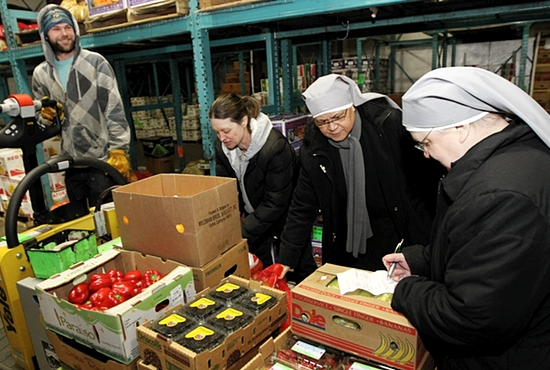 Sister Dorothy Struzinski (from right), Mother Maria Francis and Cindy Vindedahl, an employee of the Little Sisters of the Poor Holy Family Residence in St. Paul, sort through fruits and vegetables at Wholesale Produce Supply in Minneapolis with help from Kyle Johnson. The company is among many that donate to the Little Sisters to help feed the nursing home's residents and help sustain the order's mission. Dave Hrbacek/The Catholic Spirit