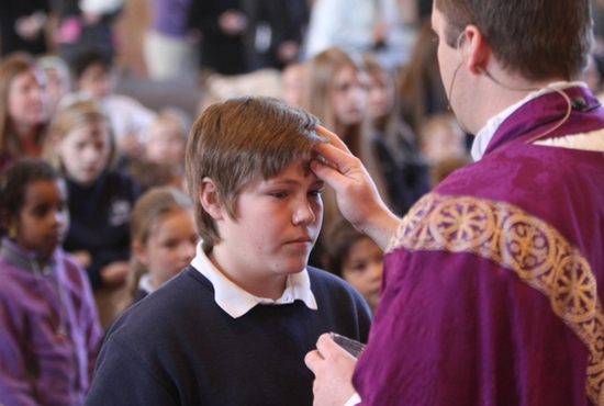 "Wyatt Gibb, an eighth-grader at St. Charles Borromeo School in St. Anthony, receives ashes from Father Brian Park, parochial administrator of the parish, during an Ash Wednesday school liturgy Feb. 18 at St. Charles. Noting in his homily that Lent coincides with Major League Baseball's spring training, Father Park encouraged students, teachers and parents to get ""back to the basics"" spiritually throughout the next 40 days. He will explain how during Sunday homilies during Lent. Dave Hrbacek/The Catholic Spirit"