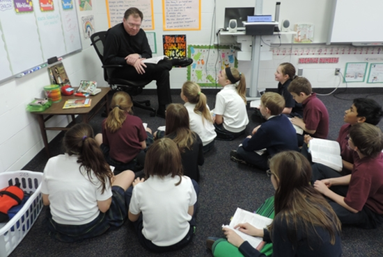 Father Michael Tix, pastor of St. John the Baptist in Savage, reads to fifth-graders at St. John the Baptist School. Photo courtesy of St. John the Baptist