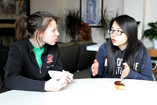 Cher Ling Tong, right, talks with her sponsor, Shawna Zielinski, at St. Lawrence-Newman. Tong will be confirmed at the Easter Vigil and complete her journey into the Church.