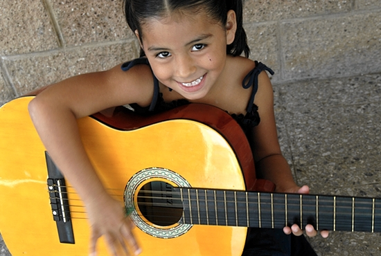A young girl from the Nuestros Pequeños Hermanos home in El Salvador plays guitar in music class. Photo courtesy NPH USA