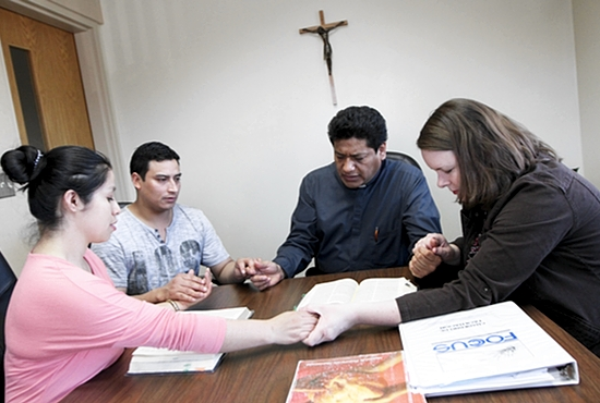 From left, Nube Hurtado Nieto, Wilson Naranjo Romero, Deacon Ramon Garcia and his wife, Suzanne, pray before a pre-marriage session at St. Stephen in Anoka. The Garcias meet regularly with both engaged and married couples. Dave Hrbacek/The Catholic Spirit