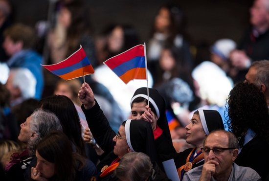 Nuns wave the Armenian flag during an April 12 Mass celebrated by Pope Francis in St. Peter's Basilica at the Vatican to mark the 100th anniversary of the Armenian genocide. CNS photo/Cristian Gennari