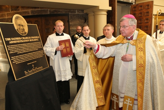 Archbishop John Nienstedt blesses a plaque in honor of Father Charles Froehle during a dedication ceremony April 30 at the St. Paul Seminary. The administration building of the seminary has been named in honor of Father Froehle, a parish priest who also served the seminary for 25 years as a professor, dean and rector. Father Froehle, who died Jan. 6 at age 77 after a lengthy illness, graduated from the seminary and was ordained a priest in 1963. In 1980, he was appointed rector and was one of the major architects of the 1987 affiliation of the seminary with the then College of St. Thomas.