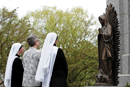 From left, Sister Mary Joseph Evans; her mother, Joan Evans; and Mother Mary Clare Roufs stand in front of a statue of Our Lady of Guadalupe in the courtyard of the Cathedral of St. Paul. Sister Mary Joseph and Mother Mary Clare, superior general, belong to the Handmaids of the Heart of Jesus in the Diocese of New Ulm. Dave Hrbacek/The Catholic Spirit