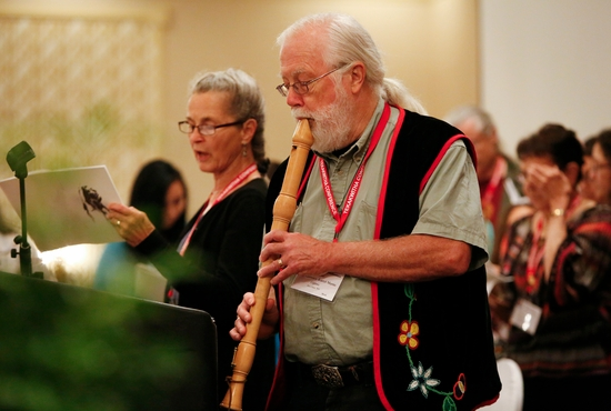 Lawrence Martin of the Gichitwaa Kateri Circle of Minneapolis plays a flute July 24, 2014, as he leads the Tekakwitha Conference in a song in the Ojibwe language at the organization's annual meeting in Fargo, N.D. CNS