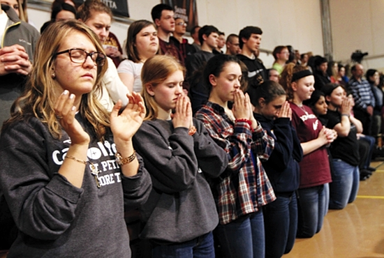 NET Ministries team leader Erika Christopher, left, of the St. Peter, Forest Lake, team prays during a Lifeline Mass at the NET Center Feb. 7. Next to her is Jessica Nieters, plus other teens from St. Peter. Dave Hrbacek/The Catholic Spirit