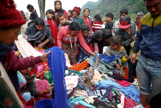 Earthquake survivors select clothes from a relief material delivery near Gorkha, Nepal, May 1. CNS photo