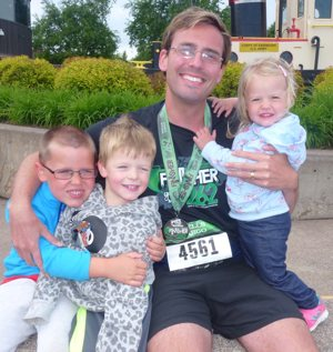 Father Erik Lundgren celebrates the completion of Grandma's Marathon with a niece and two nephews.