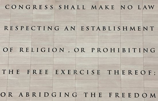 The first 20 words of the First Amendment to the U.S. Constitution are pictured etched into a wall outside the Newseum in Washington. The establishment clause prevents the formation of a national religion. The free exercise clause prohibits religious persecution and discrimination by the government. CNS