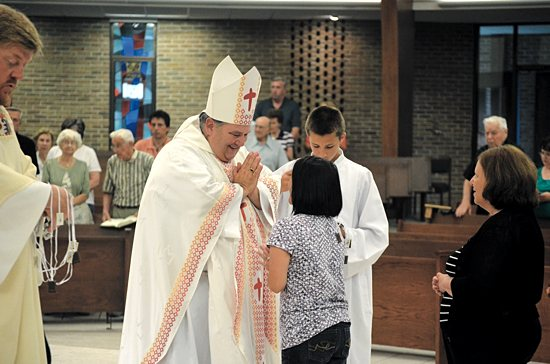 Archbishop Bernard Hebda greets a young girl when the cathedral in Gaylord, Michigan, was dedicated to St. Mary, Our Lady of Mount Carmel July 16, 2012. Courtesy the Diocese of Gaylord