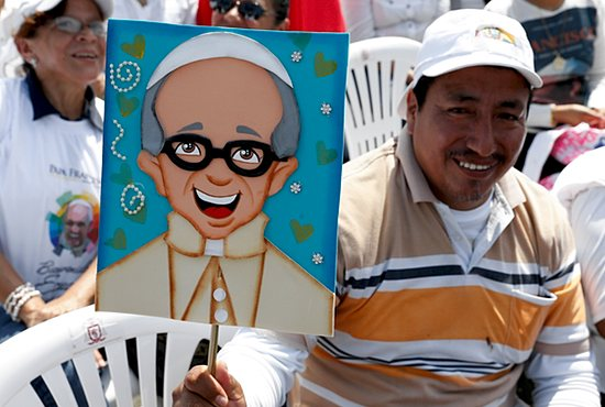A man holds an image of Pope Francis as he waits for the start of the pope's Mass in Los Samanes Park in Guayaquil, Ecuador, July 6. CNS/Paul Haring