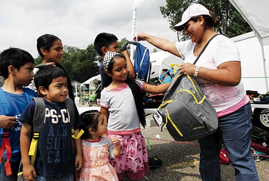 Volunteer Eugenia Torres, right, hands out donated backpacks to Alondra Lezama, center, of St. Paul and her five siblings, clockwise from left, Leonardo, Tania, Damian, Stephany and Yahanan, at an event at St. Patrick in Inver Grove Heights Aug. 22 called the Back to School Bash. Volunteers from St. Patrick and several other local churches, including Inverhills Church, which sponsored the event, handed out 1,500 backpacks filled with school supplies to grade school and high school students in need. Dave Hrbacek/The Catholic Spirit