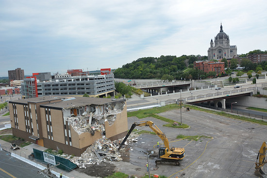 With the Cathedral of St. Paul in the background, demolition of an office building begins to make room for phase one of the expansion of the Dorothy Day Center, to include better emergency shelter and housing. (Photo courtesy Catholic Charities.)