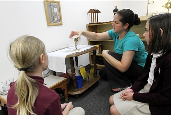 Teacher Carolyn Kohlhaas, center, shows a chalice to fifth-graders Sarah Turner, left, and Maia Irwin at the gestures altar in the Catechesis of the Good Shepherd atrium. Dave Hrbacek/The Catholic Spirit