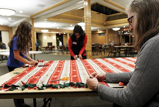 Karen Anthony, right, of St. Joseph in Miesville works on a blanket Dec. 1 at an event put on by a group called Women Inspiring Women at St. Elizabeth Ann Seton in Hastings. Women from SEAS and neighboring parishes made a total of 16 blankets, which will be given to the needy. Parishioner Jeanne Loesch collects these blankets and others for distribution through a program she started called Covered By His Love. Also working on the blanket are Amy Gapp, left, and her mother, Christina. Dave Hrbacek/The Catholic Spirit