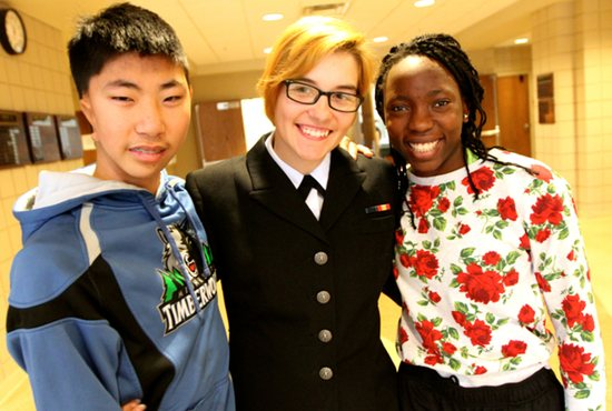 Emma Zabinski, center, takes time for a picture with siblings Thomas, left, and Martu at the Academy of Holy Angels in Richfield Dec. 18. Zabinski came home on leave from the Navy and surprised her two siblings with a visit to their school. Dave Hrbacek/The Catholic Spirit