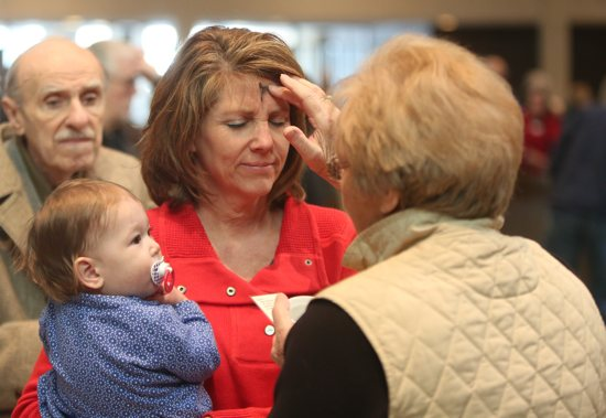 Kay McDowell places ashes on the forehead of Sue Kelly, who is holding her granddaughter Evelyn at St. Joseph in Red Wing. Dave Hrbacek/The Catholic Spirit