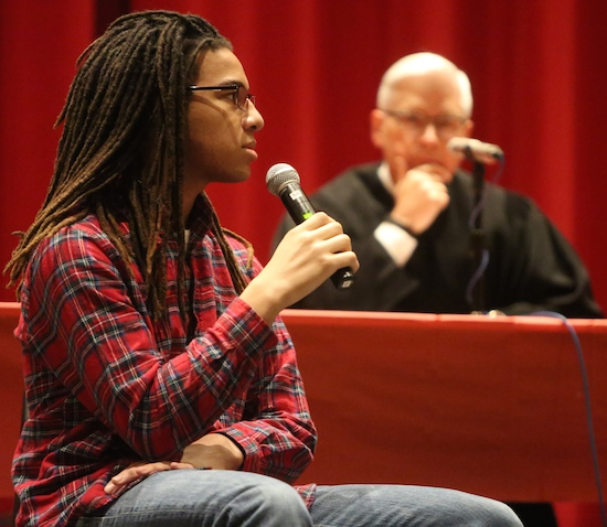 Benilde-St. Margaret's senior Obasi Lewis plays a Roman centurion who is a witness in an event at the school called Jesus on Death Row: The Trial of Jesus and American Capital Punishment. In the background is Minnesota Supreme Court Justice David Lillehaug, who acted as judge in the trial. Dave Hrbacek/The Catholic Spirit