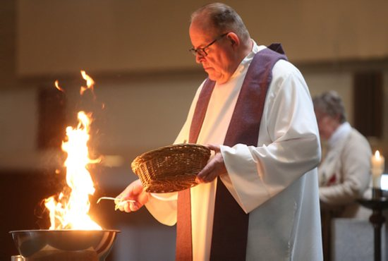 Father Thomas Kommers burns palms during an Ash Wednesday prayer service at St. Joseph in Red Wing. Dave Hrbacek/The Catholic Spirit