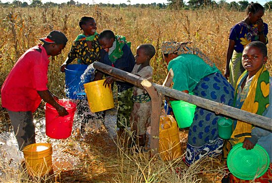 Tanzanian children collect running water from a well made possible through the Tanzania Life Project. The image has become an icon for Jim and Katie Vanderheyden, the organization's founders. John Boyer/Courtesy Tanzania Life Project