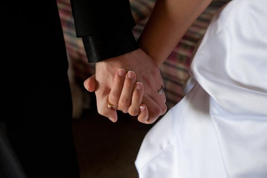 A groom and bride hold hands on their wedding day. CNS