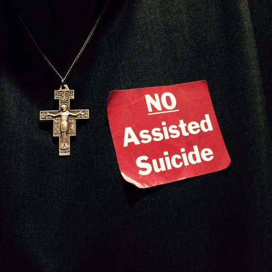 Brother Pio King, a Franciscan Brother of Peace, wears a red sticker March 16 to oppose a bill to legalize physician-assisted suicide in Minnesota. Maria Wiering/The Catholic Spirit
