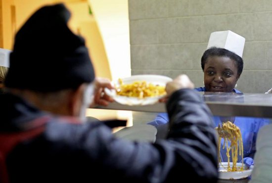 Cecile Kyenge, Italian minister for integration, serves food in the kitchen of the Astalli Center of the Jesuit Refugee Service in 2013 in Rome. Just months after his election that year, Pope Francis had said church buildings that no longer house nuns, friars, monks and other religious should be used to shelter refugees. CNS photo/Alessandro Di Meo, EPA