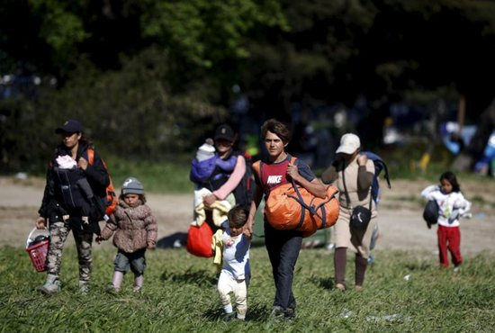People walk toward a bus April 12 at a makeshift camp for refugees and migrants at the Greek-Macedonian border near the village of Idomeni, Greece. Pope Francis asked Christians to pray for him before embarking on a one-day visit to the Greek island of Lesbos April 16. CNS photo/Stoyan Nenov, Reuters
