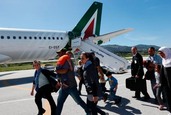 Refugees walk to board Pope Francis' plane to Rome at the international airport in Mytilene on the island of Lesbos, Greece, April 16, 2016. The pope brought 12 refugees to Italy aboard his flight. CNS photo/Paul Haring