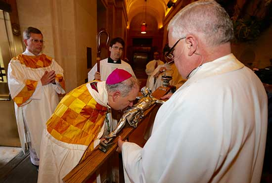 Archbishop Bernard Hebda kisses a crucifix held by Father John Bauer, pastor of the Basilica of St. Mary in Minneapolis, at the start of the Rite of Reception May 12 at the Basilica. Archbishop Hebda knocked on the outside door to start the event, then was presented with the crucifix upon entering.
