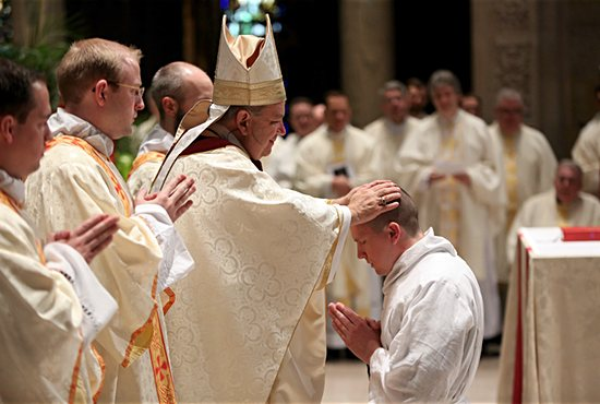 Archbishop Bernard Hebda lays hands on Bryce Evans to ordain him a transitional deacon May 14 at the Basilica of St. Mary in Minneapolis. Also ordained transitional deacons were  Paul Baker, Nicholas Froehle, Matthew Quail, Timothy Sandquist, Matthew Shireman, Brandon Theisen, Chad VanHoose and Benjamin Wittnebel. Dave Hrbacek/ The Catholic Spirit
