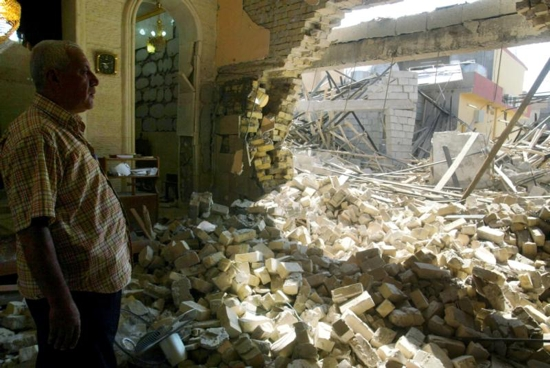 An Iraqi man inspects the damage in 2011 at a Catholic church after attacks in Kirkuk. Despite predictions that Christianity could be wiped out of his war-torn homeland within five years, Chaldean Archishop Yousif Mirkis of Kirkuk said he believes in God's ultimate preservation. CNS photo/Khalil Al Anei, EPA