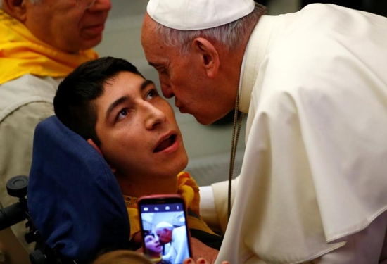 Pope Francis kisses a disabled young man during a special audience with members of Doctors with Africa at the Vatican May 7. CNS photo/Tony Gentile, Reuters