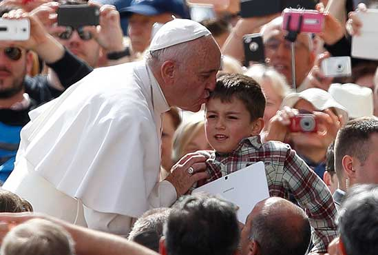 Pope Francis greets a boy carrying a tablet during his general audience in St. Peter's Square at the Vatican May 25. CNS/Paul Haring