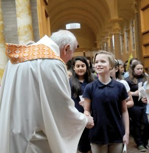 Caroline Miltich from St. Andrew School in Elk River, Minn., and other students are greeted by Bishop Donald J. Kettler of St. Cloud, Minn., after a May 9 prayer service in the Sacred Heart Chapel at St. Benedict's Monastery in St Joseph, Minn. About 350 students from 17 schools participated in the pilgrimage. CNS photo/Dianne Towalski, The Visitor