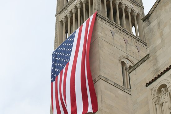 A large American flag is seen hanging from the bell tower of the Basilica of the National Shrine of the Immaculate Conception in Washington July 4, 2015. The U.S. bishops' fifth annual Fortnight for Freedom opens June 21. CNS/Bob Roller
