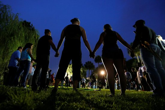 People hold hands in a circle during a June 12 vigil in an Orlando, Fla., park following a mass shooting at the Pulse gay nightclub in that city earlier that morning. CNS/Carlo Allegri, Reuters