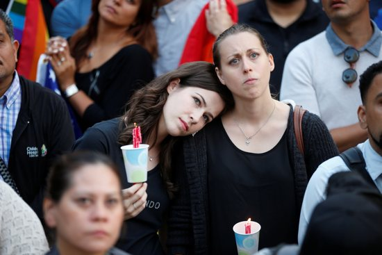 Women hold candles during a June 13 vigil in Los Angeles for the victims of the mass shooting at the Pulse gay nightclub in Orlando, Fla. A lone gunman, pledging allegiance to the Islamic State terrorist group, killed 49 people early June 12 at the nightclub. CNS/Lucy Nicholson, Reuters